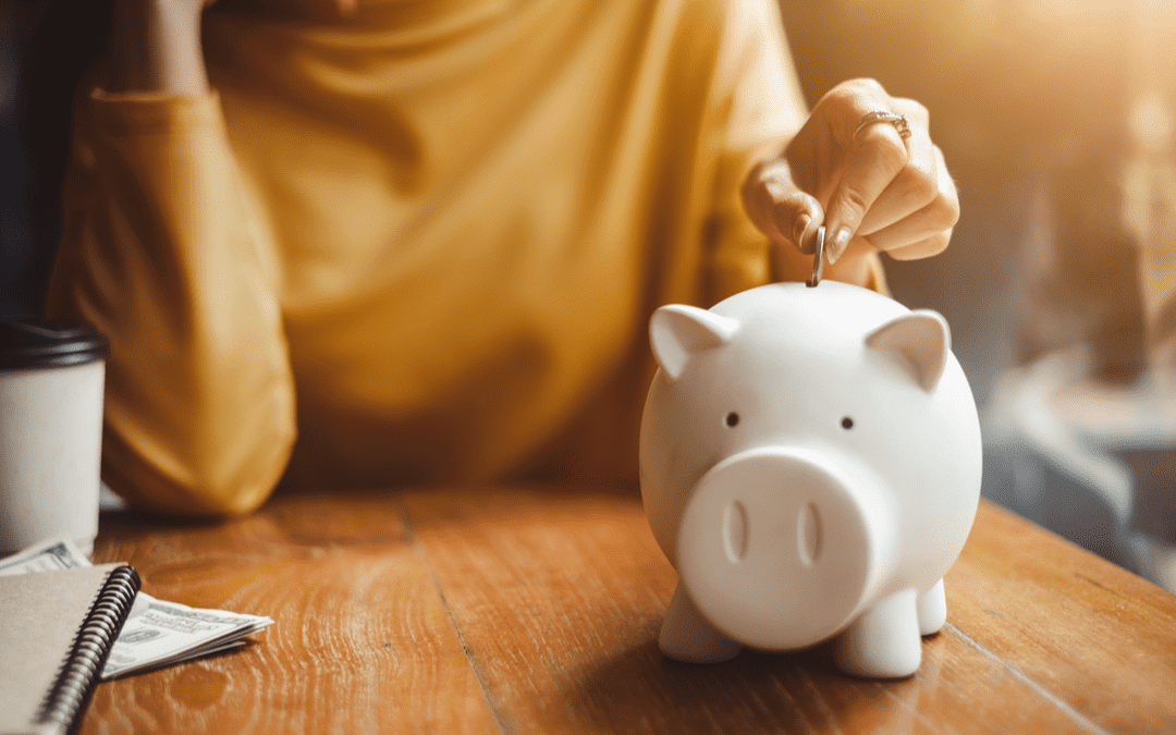 Person wearing yellow shirt dropping coin into piggy bank on desk