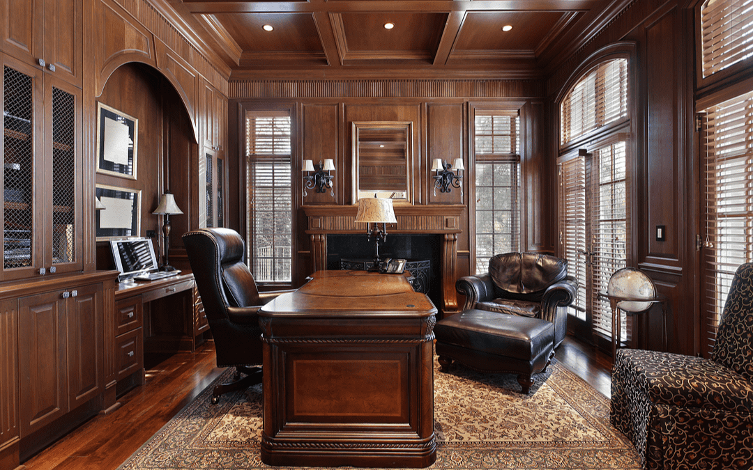Home office with wood paneled ceilings, built-ins, and tall windows.