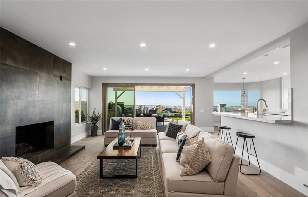 Living Room With Focal Point Fireplace Opening To Backyard With Endless Views