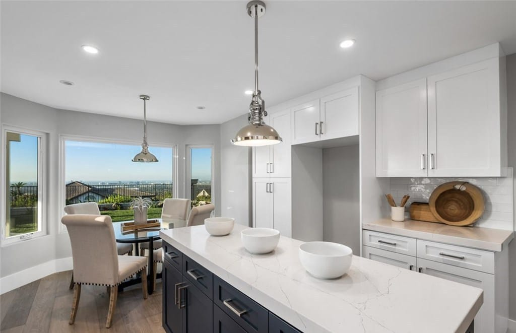 Newly Remodeled Kitchen With Pendant Lighting And Large Window Overlooking Backyard With City Views